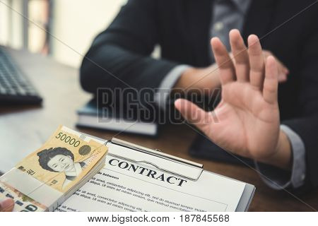 Businessman refusing money South Korean won that come with contract paper - anti bribery and corruption concepts