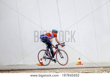Rosa Khutor, Russia -  May 7, 2017: athlete cyclist multi-day cycling riding on road with orange traffic cone in race Spring mountain marathon