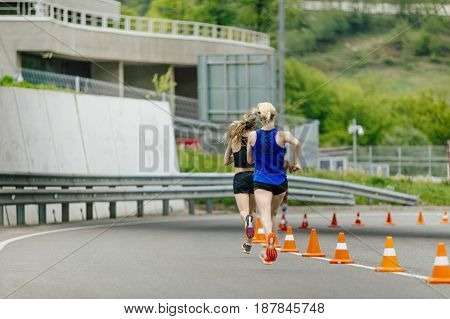 Rosa Khutor, Russia -  May 7, 2017: back two young women running in road with traffic cones safety in race Spring mountain marathon
