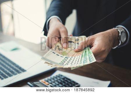 Businessman giving money South Korean won bills