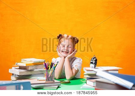 The teen girl with lot of books sitting at table on orange studio background. The education and back to school concept