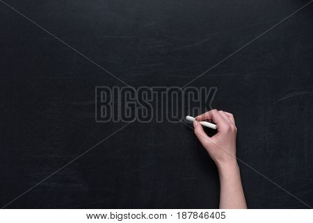Human Hand Writing With Piece Of Chalk On Black Chalkboard