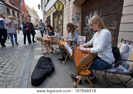 VILNIUS LITHUANIA - MAY 20: Unidentified musician play Lithuanian plucked string instrument (Kankles) in Street Music Day on May 20 2017 in Vilnius. Its a most popular event on May in Vilnius.
