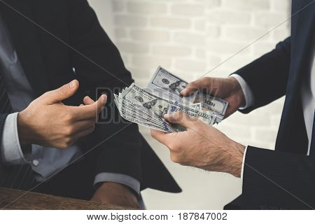 Businessmen secretly passing money to his partner - bribery and corruption concepts