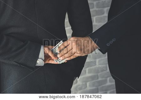 Businessman secretly giving money to his partner behide the back - bribery and corruption concept