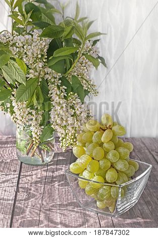 Bunch of white grapes on the table in a transparent glass container in the early morning light from the window and beautiful shadow.