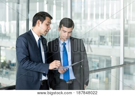 Two businessmen standing and discussing work at office building corridor