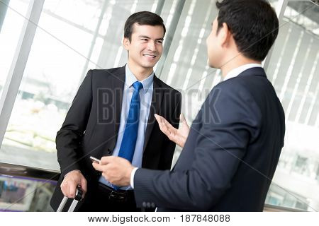 Two businessmen talking at hallway of airport terminal
