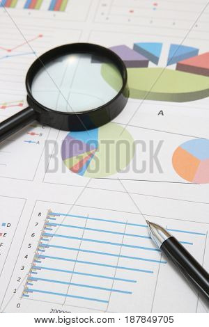 Business concept. Charts, diagrams, tables with pen and magnifying glass. Workplace for the business person.