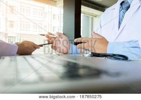 Two Doctors Discussing Patient Notes In An Office Pointing To A Clipboard With Tablet As They Make A