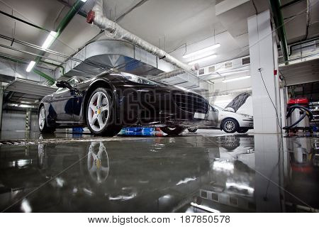 Side view of black colored shiny sportcar in a carwash. Horizontal indoors shot.