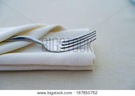 Closeup fork in white folded napkin on restaurant table