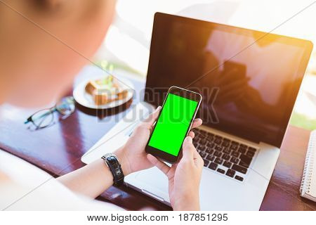 Hand holding smartphone green screen orange sunshine. smartphone vintage tone. smartphone black coler. woman using smartphone. using smartphone in coffee shop. using smartphone green screen. girl using smartphone.
