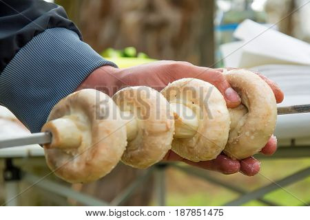 Close up man hand putting mushrooms on skewer for grilling