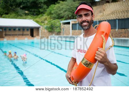 Portrait of lifeguard standing with lifebuoy near poolside