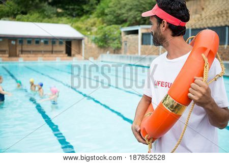 Lifeguard with lifebuoy looking at students playing in the pool on a sunny day