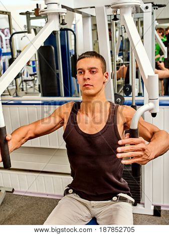 Training apparatus gym for man pumping muscles sitting on bench. Chest Exercise with weight. He takes his hands in front of his chest in fitness center.