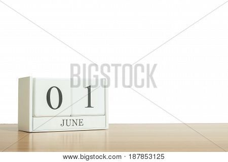 Closeup surface white wooden calendar with black 1 june word on blurred brown wood desk isolated on white background with copy space selective focus at the calendar