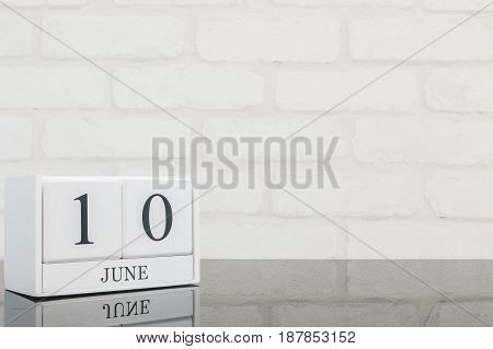 Closeup white wooden calendar with black 10 june word on black glass table and white brick wall textured background with copy space selective focus at the calendar