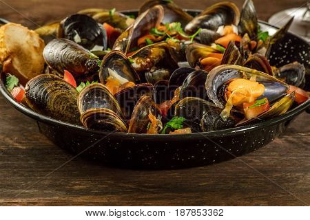 A closeup of a skillet of marinara mussels on a dark rustic background