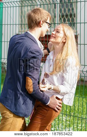 Young European Attractive Couple Is Standing And Hugging Close To Green Fence Under Sun. Beautiful W
