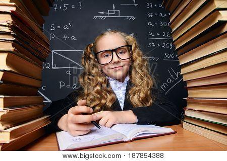 Portrait of a smart schoolgirl in glasses posing with books over school blackboard. Educational concept.