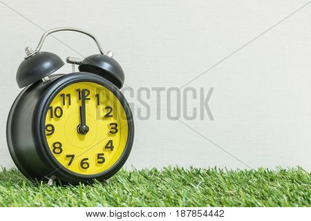 Closeup black and yellow alarm clock for decorate in 12 o'clock on green artificial grass floor and cream wallpaper textured background with copy space