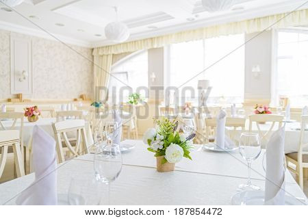Elegant served table with wine glasses, napkins and flowers in modern restaurant