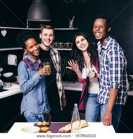 Happy smiling young friends at kitchen, two interracial couples live together. Fun pastime, cook, communicate and laugh concept.