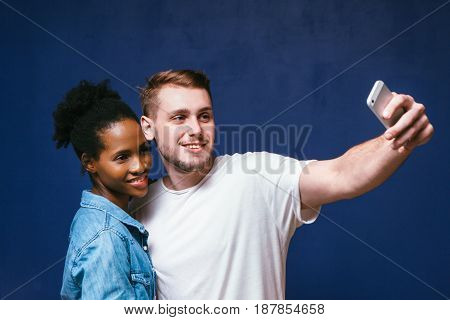 White man and black woman make selfie with smartphone on blue background, fun and joy. Young smiling interracial couple happy together. Social network addiction concept