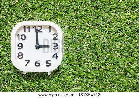 Closeup white clock for decorate in 3 o'clock on green artificial grass floor textured background with copy space