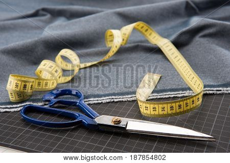 Close-up View Of Fabric, Scissors And Measuring Tape For Dressmaking