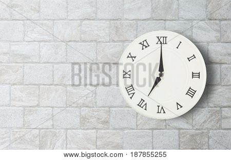 Closeup white clock for decorate in 7 o'clock on old brick wall textured background with copy space in interior concept