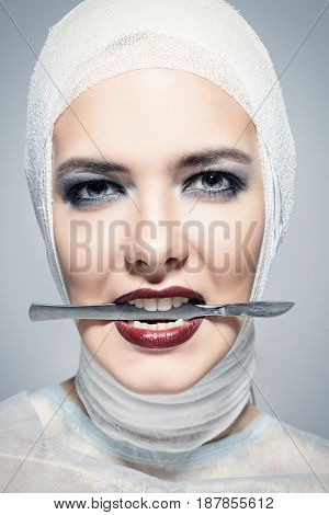 Close-up portrait of an attractive young woman in bandages holding a scalpel. Beauty, fashion and medicine, plastic surgery. Studio shot.