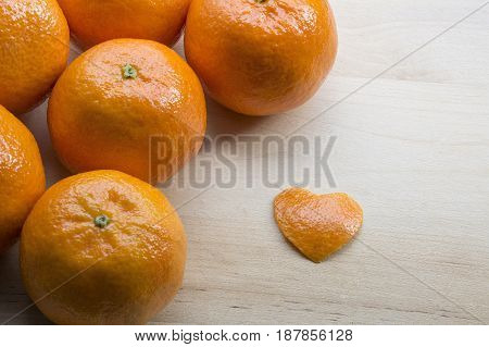 Several sweet mandarins with a peel in form of heart are on the wooden background