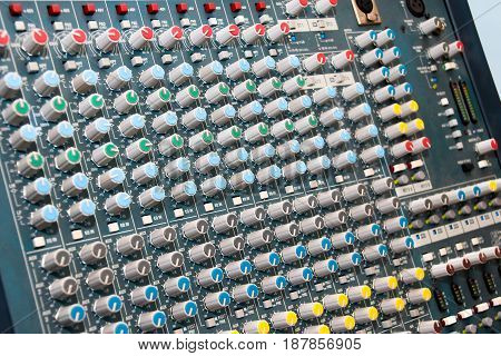 Sound mixing console with lots of buttons and knobs.