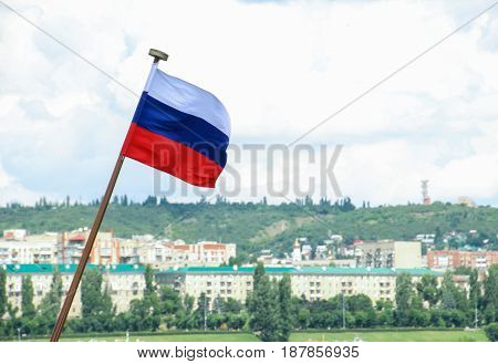 Russian flag on the background of the city of Saratov, Russia. The focus in the foreground. Blurred background. Summer day
