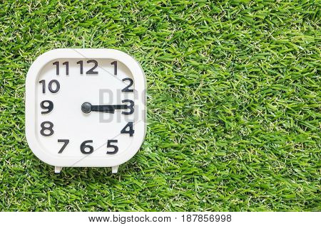 Closeup white clock for decorate show a quarter past three o'clock or 3:15 p.m. on green artificial grass floor textured background with copy space