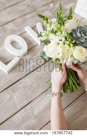 Woman hold bunch with white roses and succulent on light grey background. Word love under bouqet. Decor, photo for social media, gift, wedding, relationships concept.