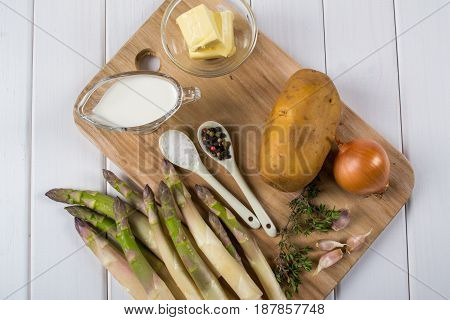 Vegan ingredients for cooking soup from asparagus. Recipe on white wooden table