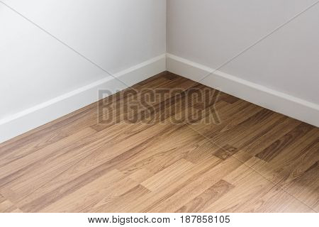 Laminated wood floor with white wall, room's corner