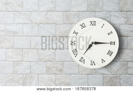 Closeup white clock for decorate show a quarter past seven o'clock or 7:15 a.m. on old brick wall textured background with copy space in interior concept