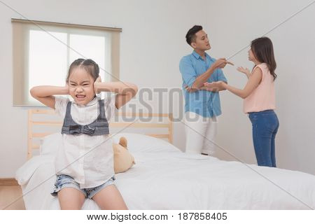 Asian Little Girl Sad And Closing Her Ears While Parent Quarrelling And Fighting In Bedroom.photo De