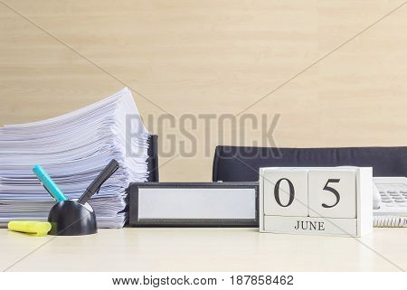 Closeup white wooden calendar with black 5 june word on blurred brown wood desk and wood wall textured background in office room view with copy space selective focus at the calendar