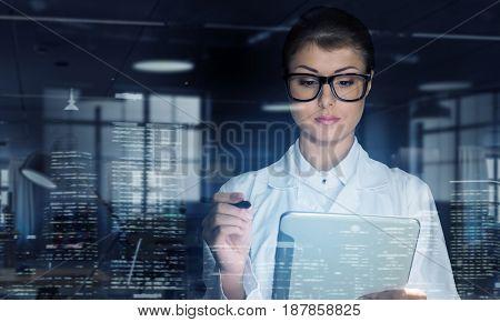 Woman doctor use tablet . Mixed media . Mixed media