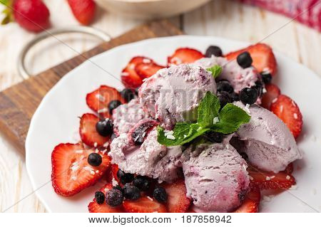 Ice cream with wild berries strawberries and mint.