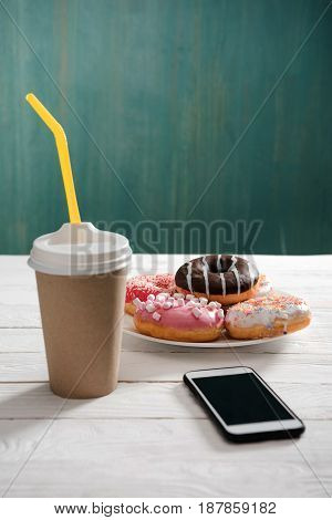 Unhealthy Breakfast With Coffee Cup, Plate Of Frosted Donuts And Smartphone With Black Screen On Woo