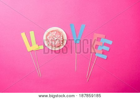 Top View Of Love Sign Made From Letters And Cream Glaze On Donut Isolated On Pink.  Junk Food Backgr
