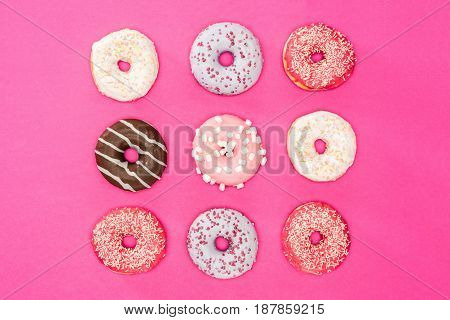 Overhead View Of Sweet Donuts With Colorful Glaze On Pink Surface. Donuts Chocolate Background