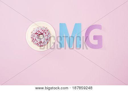 Top View Of Omg Sign Made From Letters And Icing Donut Isolated On Pink. Chocolate Donuts Background